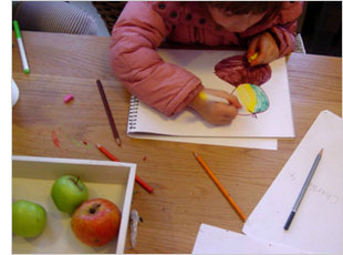 "Toddler drawing an apple for the letter ""A"""