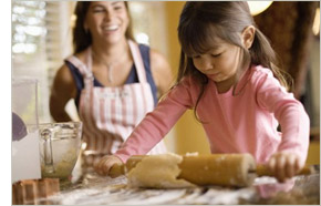 Young girl helping her mother bake
