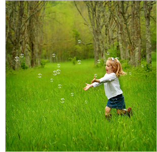 Young child chasing bubbles